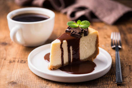 Cheesecake with chocolate sauce and cup of black coffee on a wooden table. Tasty snack or coffee time with slice of cake