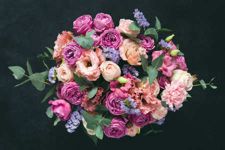 Beautiful bouquet of pink purple peonies, roses and eucalyptus isolated on black background. Top view