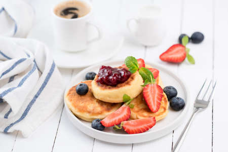 Cottage cheese pancakes or Syrniki with strawberries, blueberries, berry jam and cup of black coffee espresso. Tasty breakfast on white table