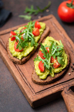 Healthy toast with avocado, tomato, arugula on a wooden serving board. Vegan, vegetarian food