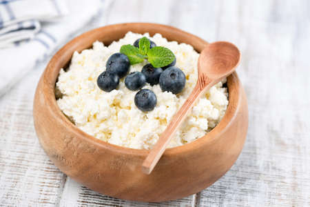 Closeup view of Cottage Cheese or Tvorog in wooden bowl on white wooden background. Closeup view. Cottage cheese with blueberries 스톡 콘텐츠