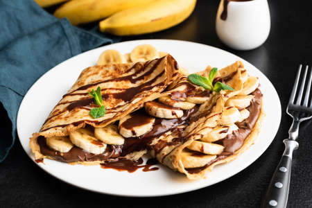 Tasty crepe with hazelnut chocolate spread and banana on white plate Imagens