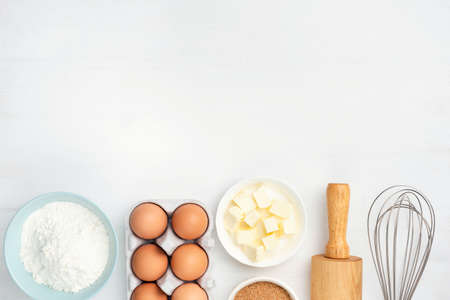Baking ingredients and kitchen utensils on white