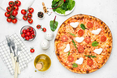 Italian pizza with heart shaped mozzarella, tomatoes and basil on white background. Table top view delicious pizza