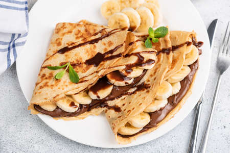 Crepes or blini stuffed with chocolate hazelnut spread, banana on a white plate. Closeup view