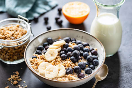 Granola, Fruits, Berries in bowl on black concrete background. Healthy breakfast cereals. Concept of dieting, healthy eating, clean eating