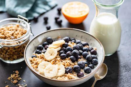 Muesli, frutta, bacche in ciotola su fondo di cemento nero. Cereali da colazione sani. Concetto di dieta, alimentazione sana, alimentazione pulita