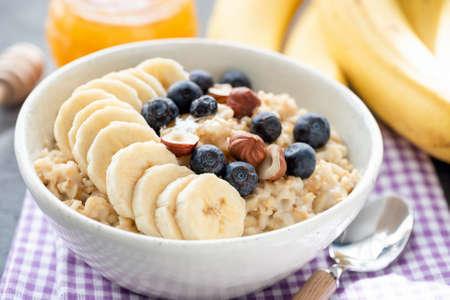 Tasty Oatmeal Porridge Bowl With Banana, Blueberry, Hazelnuts And Honey. Vegan Breakfast Food For Healthy Diet