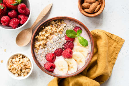 Acai smoothie bowl with superfood. Fruit smoothie with banana, raspberry, chia seed and granola in coconut bowl, top view