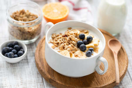 Healthy breakfast cereals granola with milk and fruits in a bowl on wooden table background. Closeup view, selective focus