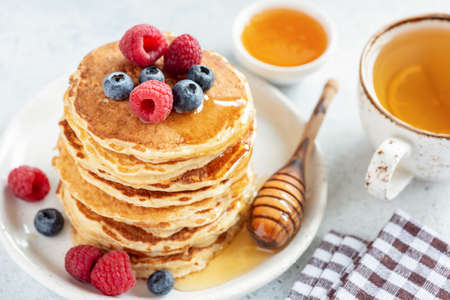Homemade pancakes topped with berries and honey served with cup of green tea with lemon. Closeup view. Tasty breakfast food Stock Photo