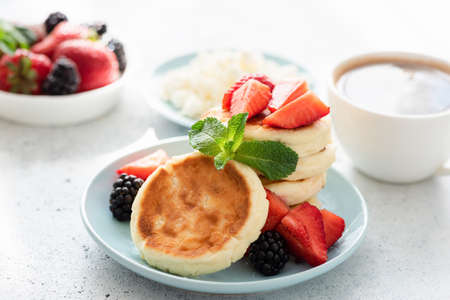 Cottage cheese pancakes syrniki with fresh berries and cup of coffee. Tasty healthy breakfast food