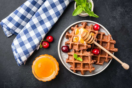 Delicious belgian waffles with honey and sweet cherries on a plate, black concrete