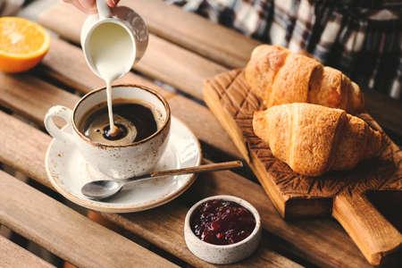 Sahne in eine Tasse schwarzen Kaffee gießen. Leckerer Frühstückstisch mit Croissants, Marmelade und Kaffee