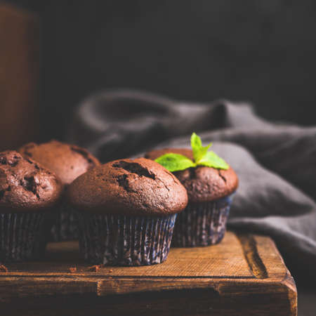 Chocolate cakes or muffins on wooden board, closeup view, toned image