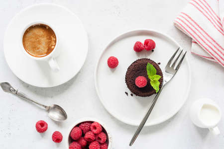 Chocolate cake served with raspberries and cup of espresso coffee on white concrete table Stock Photo