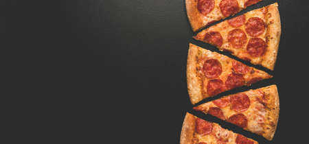 Pepperoni pizza slices on black Imagens