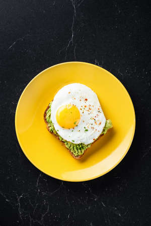 Sunny side up egg and mashed avocado on toasted sandwich bread. Stock Photo