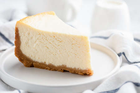 Piece of plain New York Cheesecake on white plate, closeup view. Imagens