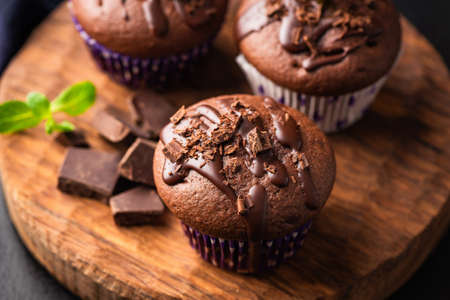 Double chocolate muffins covered with melted chocolate on a wooden