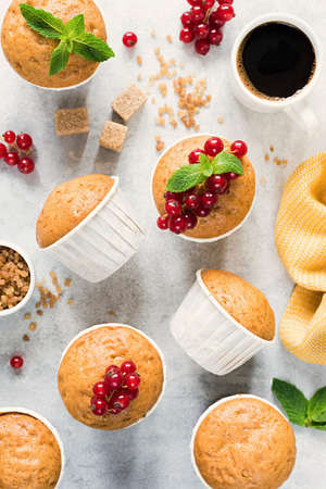Basic homemade vanilla muffins decorated with red currant berries on grey concrete Reklamní fotografie