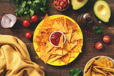 Corn tortilla chips Nachos with tomato sauce on plate.