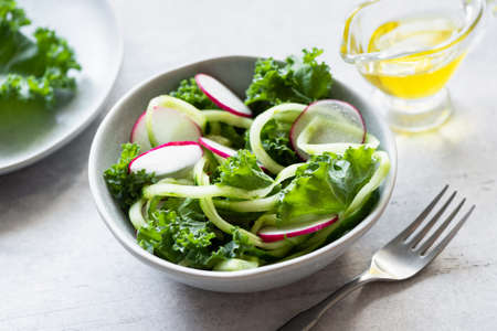 Vegan green salad with kale, cucumber and radish dressed with extra virgin olive oil