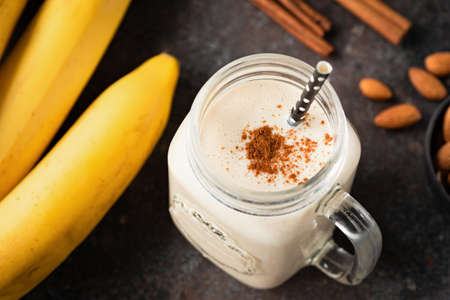 Healthy banana cinnamon smoothie or shake in glass cup on dark Reklamní fotografie