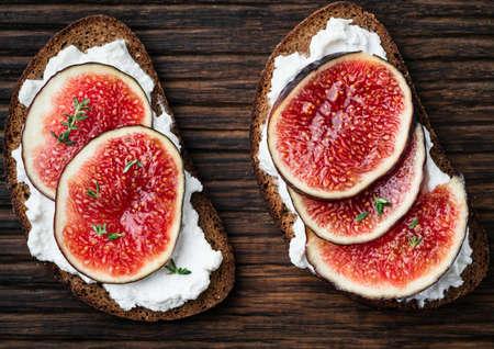 Healthy appetizer rye bruschetta with figs, ricotta cheese and thyme on a wooden 写真素材 - 129779625