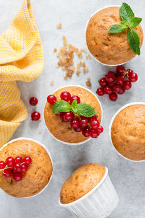 Tasty muffins on grey  decorated with red berries and mint leaf.