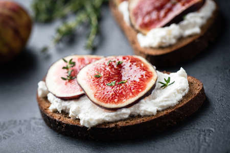 Rye bread toast with figs and ricotta cheese on black slate Фото со стока - 129779756