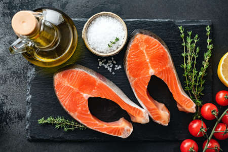 Salmon steaks and spices for cooking on black slate Stockfoto