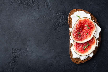 Fig and cottage cheese on rye bread toast on black concrete 写真素材 - 129780593