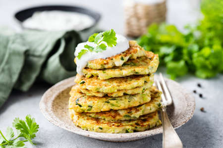 Vegetable zucchini fritters in stack topped with sour cream.