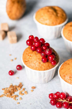 Homemade muffins in white paper cups decorated with red currant berries. Reklamní fotografie