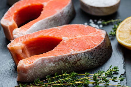 Fresh fish. Raw uncooked salmon steaks on slate.