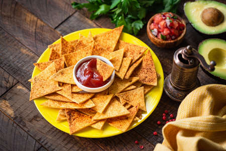 Mexican tortilla chips Nacho with tomato sauce and salsa on yellow plate
