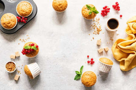 Tasty homemade muffins with red berries and brown sugar and cup of coffee espresso on bright grey concrete