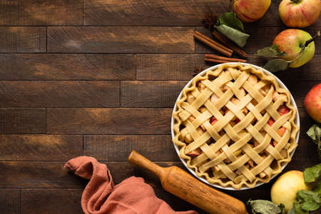 Unbaked apple pie with lattice crust on brown wooden table before. Autumn season holiday baking. Top view copy space