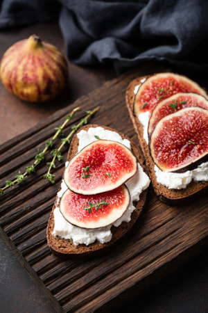 Rye toast with ricotta cheese and figs on wooden cutting board. Healthy snack Stock fotó
