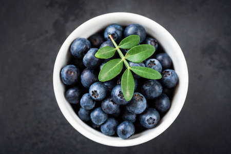 Fresh blueberries in bowl on black background, table top view