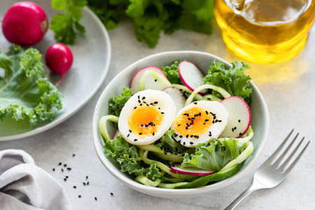 Healthy salad with egg, radish, kale and cucumber in bowl. Diet fresh spring salad Banco de Imagens
