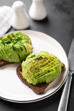 Rye bread toast with avocado on white plate. Healthy vegan vegetarian food