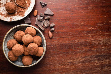 Homemade chocolate truffles on wooden table. Top view with copy space for text, recipe Reklamní fotografie