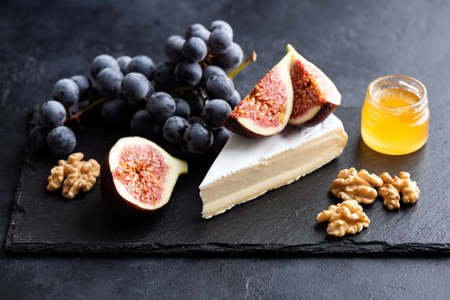 Brie or camembert cheese board with walnuts, grapes, figs and honey served on black slate plate. Gourmet appetizer Banco de Imagens