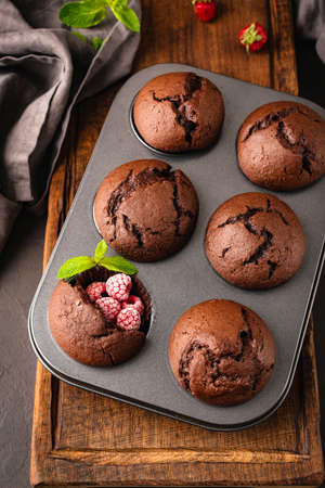 Chocolate muffins with raspberry in metal muffin baking tin