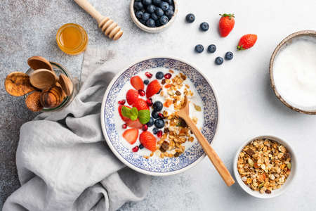 Healthy breakfast yogurt bowl with granola and berries on grey concrete