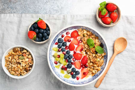 Healthy breakfast yogurt bowl with berries blueberry, strawberry, kiwi, pomegranate and granola on linen texture.