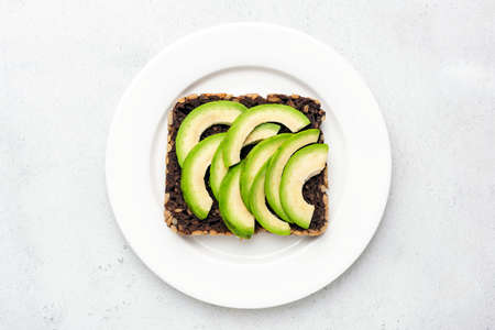 Sliced avocado on whole grain rye bread with seeds on white plate