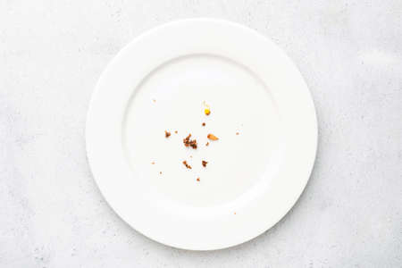 White plate with crumbs leftovers on grey concrete background. Top view